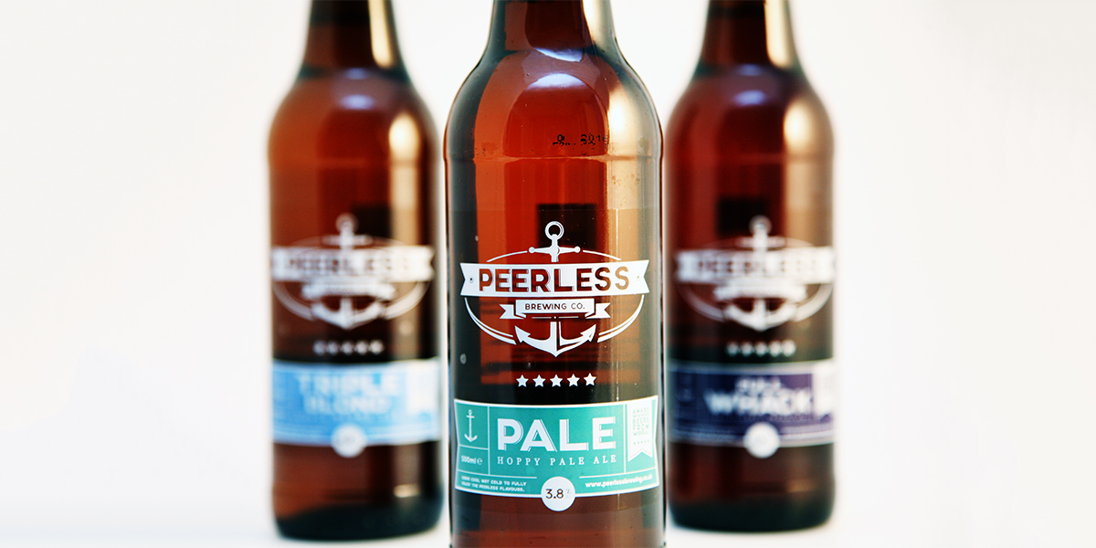 Close up image of 3 Peerless Brewery bottles: Triple Blond, Full Whack and a zoom in on Pale